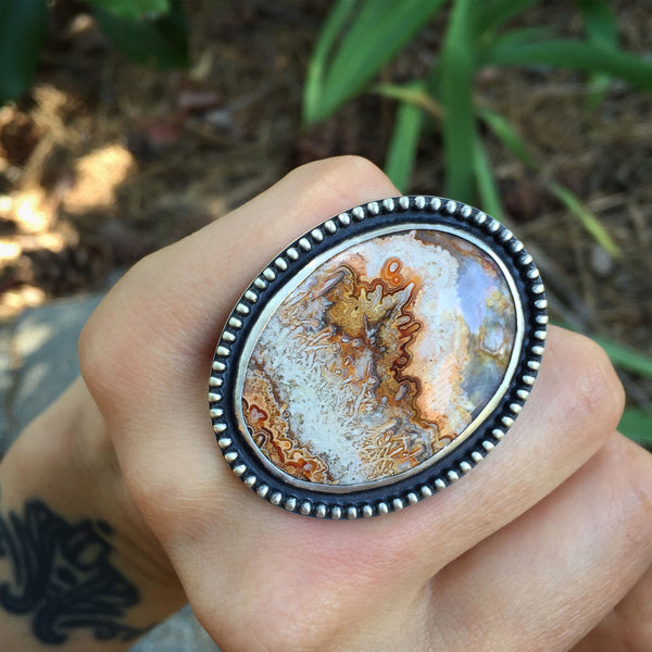 The Fire Sea Ring is handcrafted from sterling silver and features an orange crazy lace agate stone.  The ring is handmade by Nikki Leigh of Osa Metal Studio.