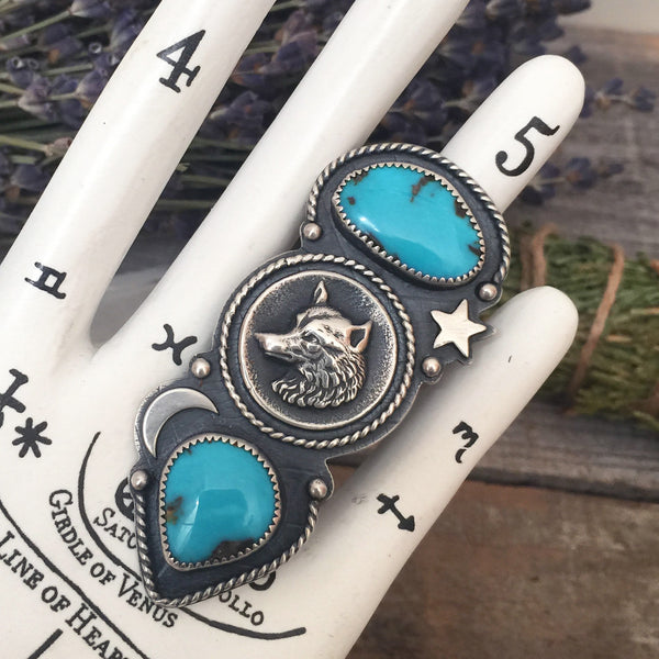 The Wild Wanderer Ring is handcrafted from sterling silver and natural blue Candelaria turquoise stones.  It features a sterling silver casting of an antique wolf button.  This cosmic Southwestern ring is handmade by Nikki Leigh of Osa Metal Studio.