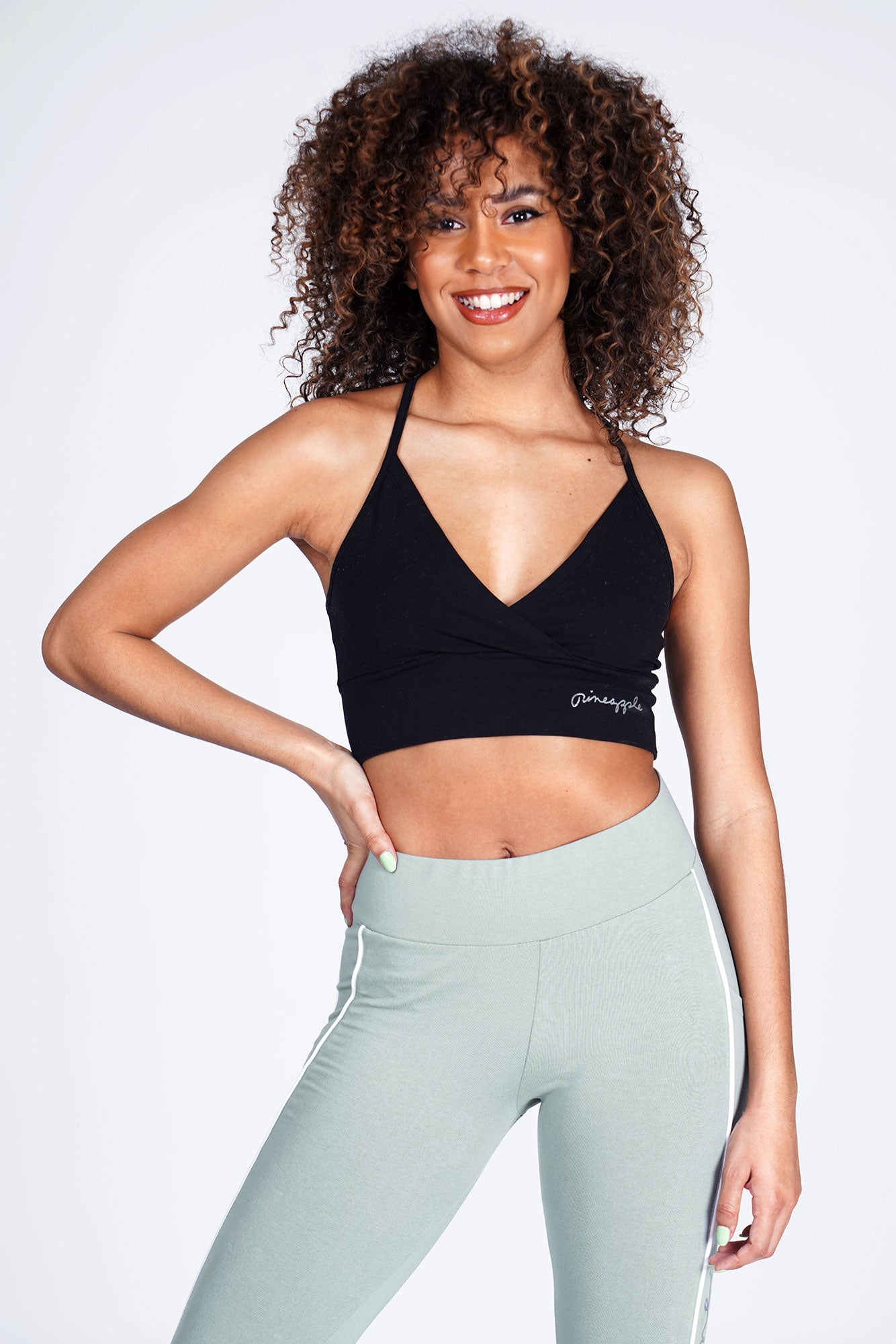 Woman wearing Pineapple Black 'V' Wrap Crop Top with sage green leggings