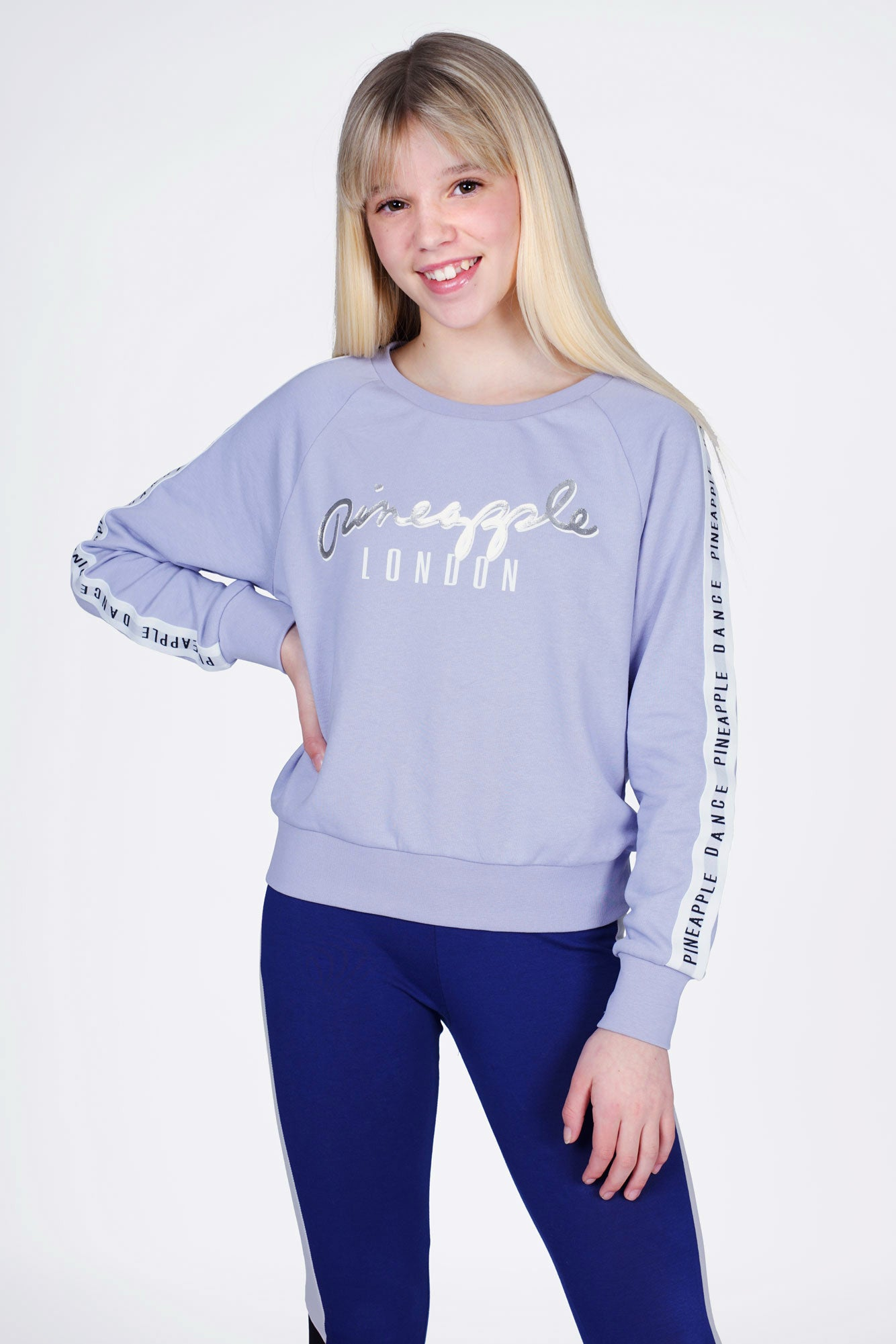 Girl wearing Pineapple Blue Jacquard Sweat Top with silver logo and white logo sleeve stripes