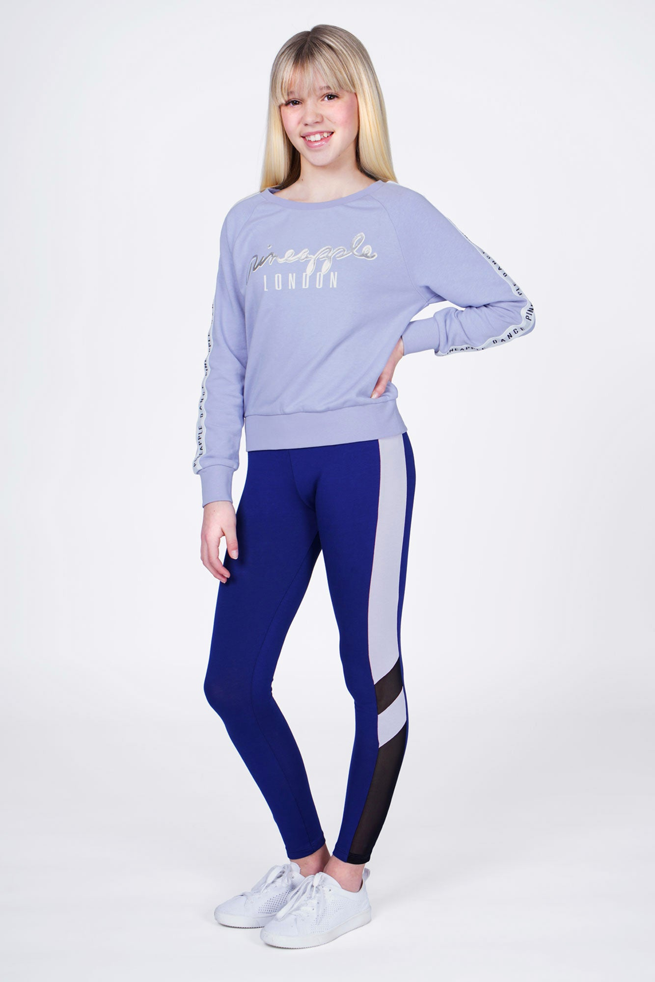 Girl wearing Blue Jacquard Sweat Top with silver logo and white logo sleeve stripes, and Blue Mesh Panel Leggings