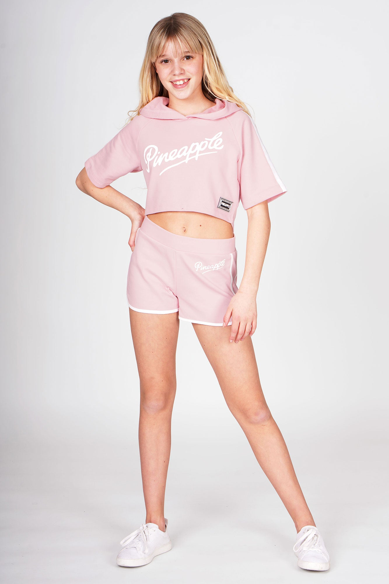 Girl wearing Pink Sporty Shorts and pink short sleeve crop hoodie