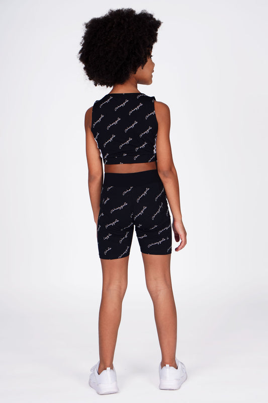 Girl wearing All-over Print Black Cycling Shorts and Black All-over Print Crop Top, full back view