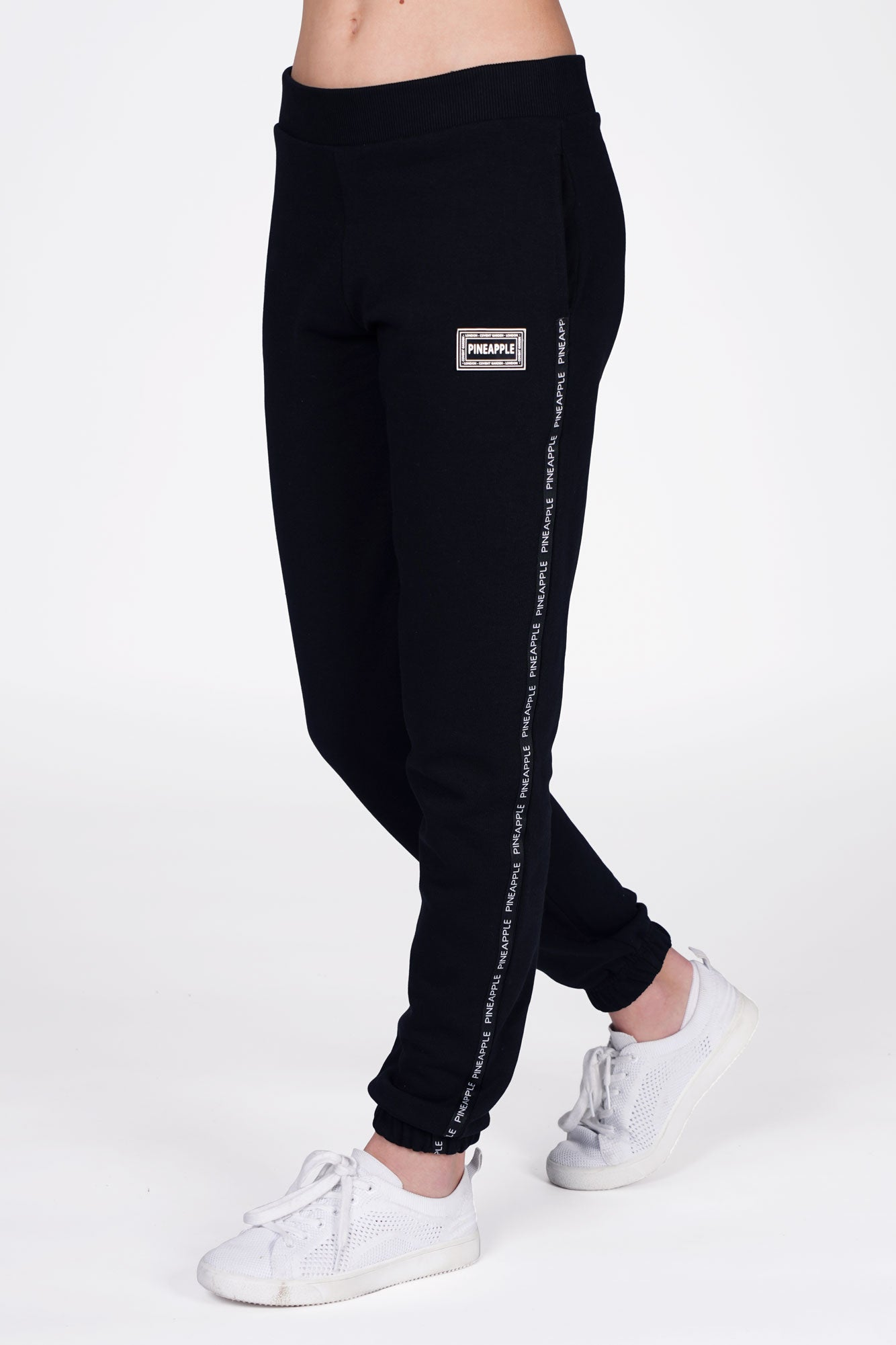 Girl wearing Pineapple Black Tape Joggers with white stripe, cropped side view