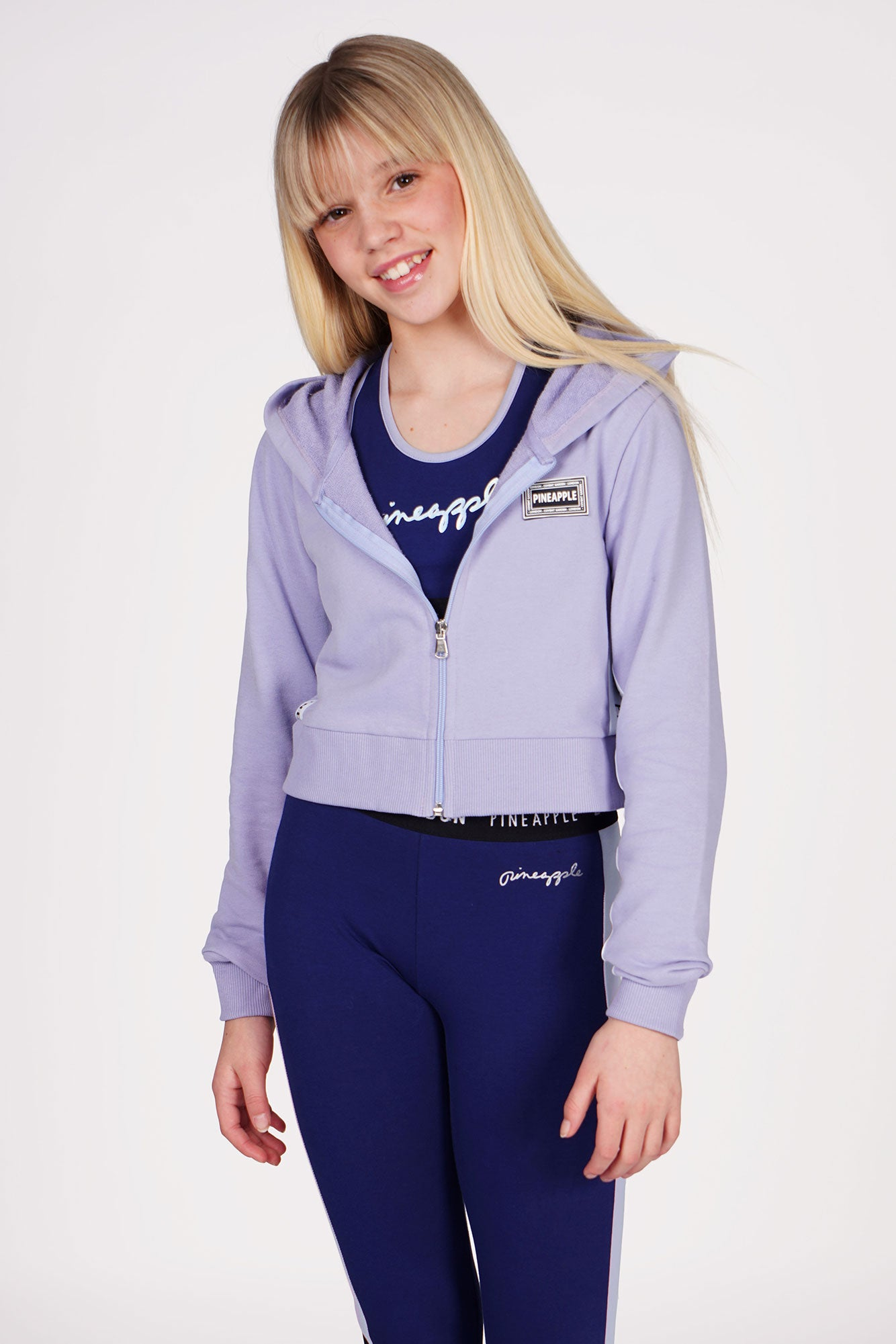 Girl wearing Lilac Blue Pineapple Tape Zip Hoodie with Navy Blue Panel Racer Bra Top and Navy Blue Mesh Panel Leggings