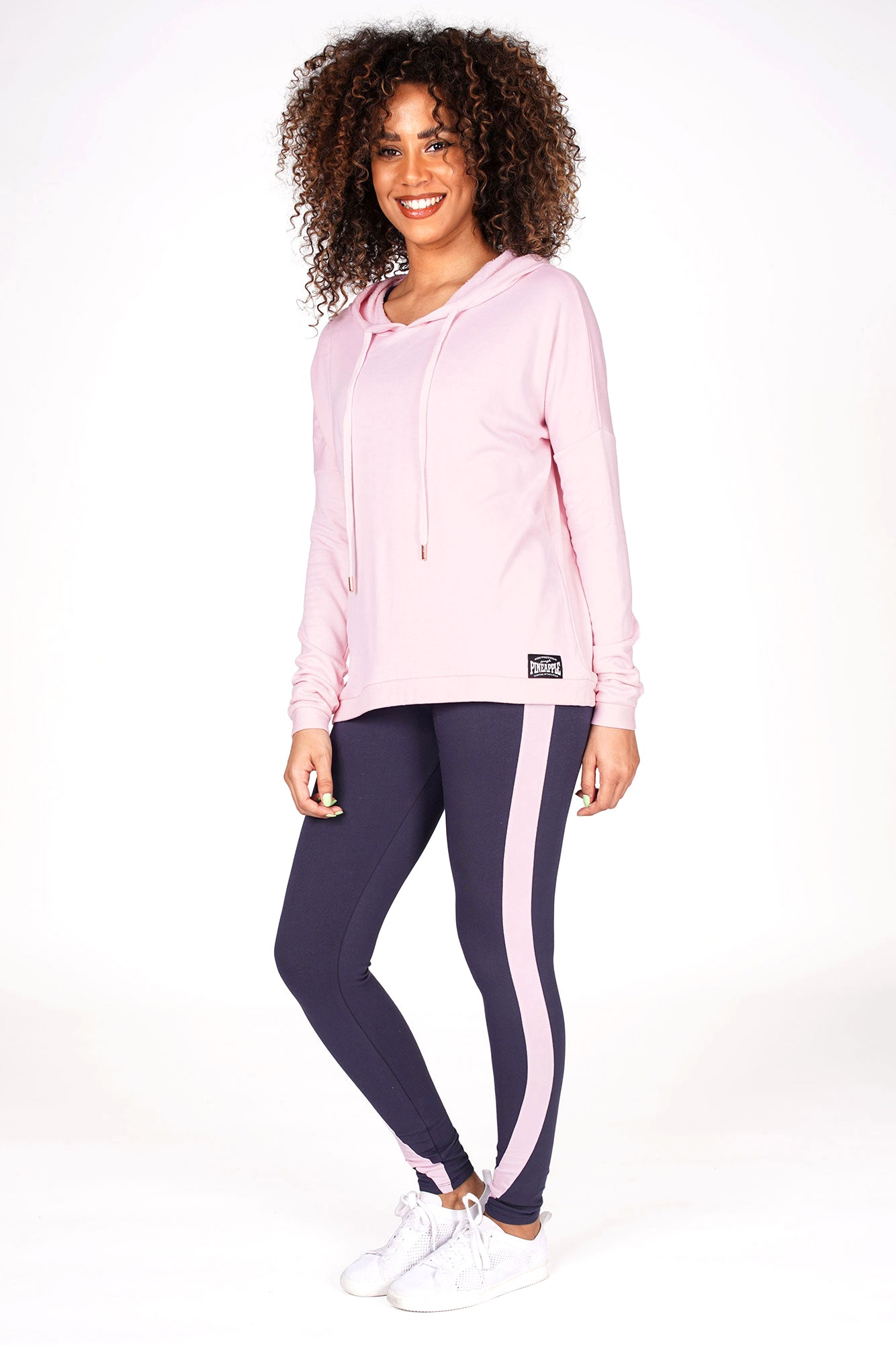 Woman wearing Pink Dip Hem Hoodie and charcoal racer stripe leggings