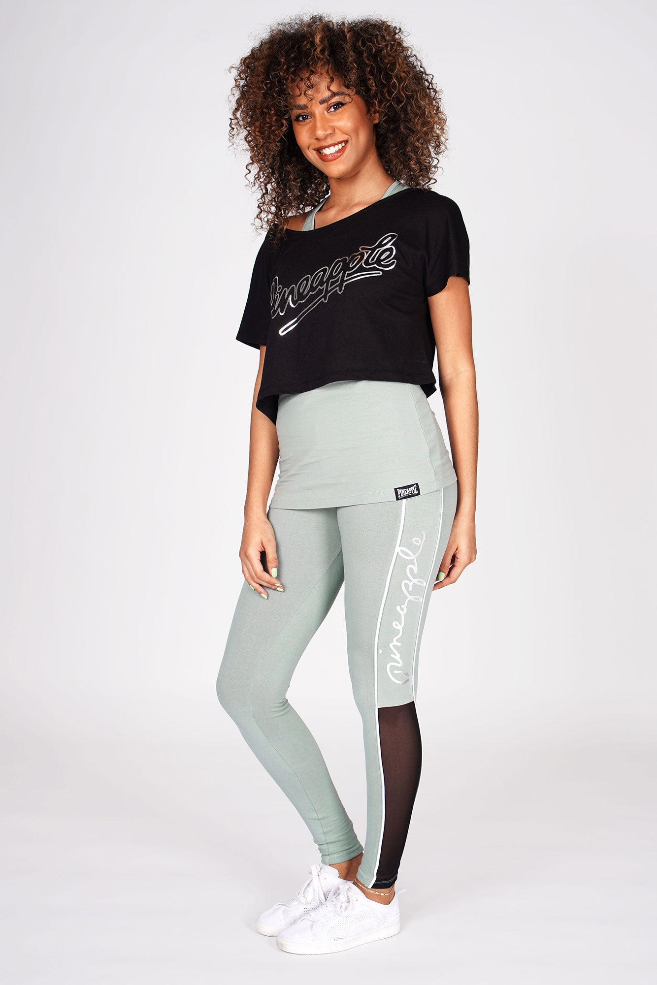 Woman wearing Sage Double Layer Top Set and Sage Piping Pocket Leggings