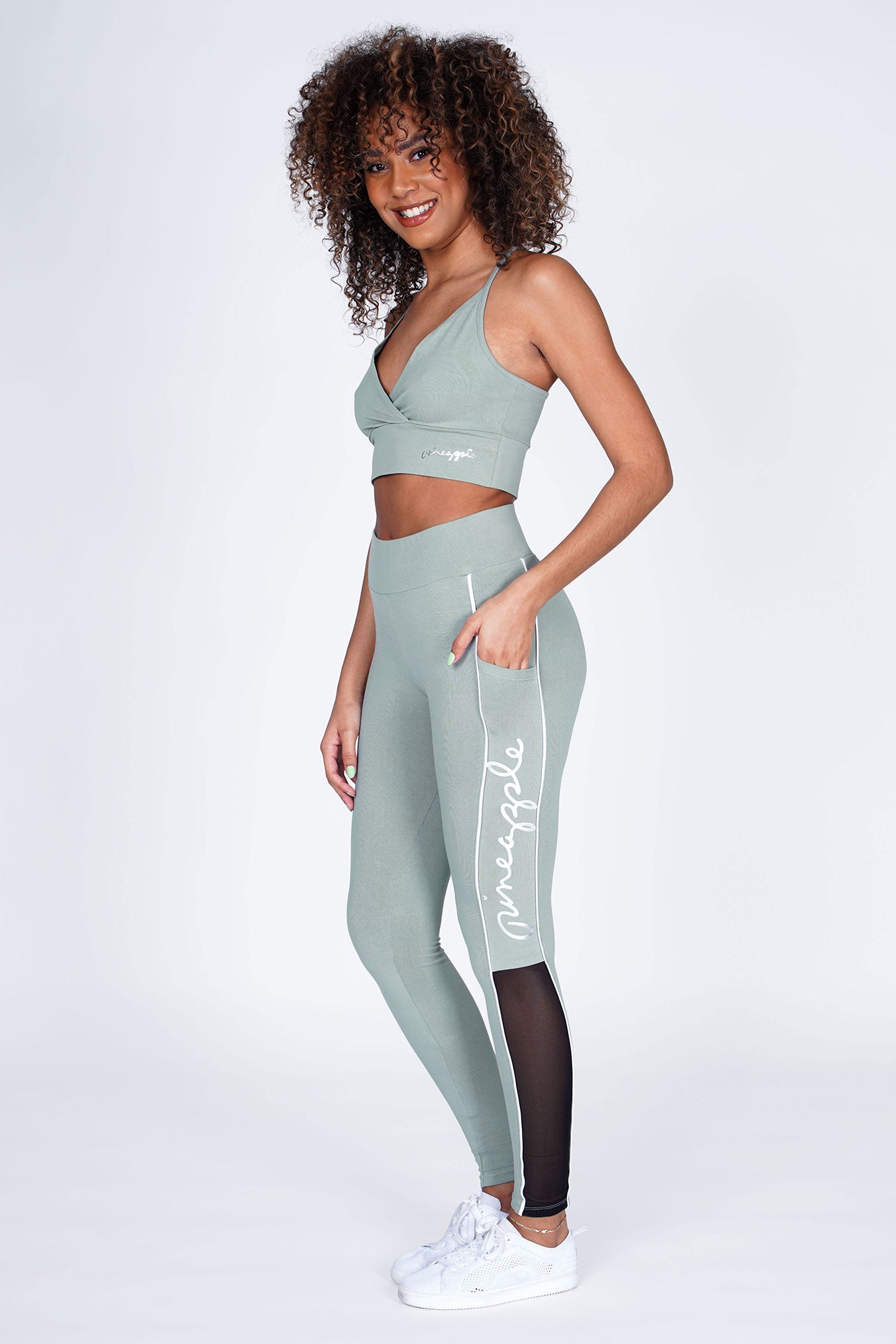 Woman wearing sage Green 'V' Wrap Crop Top and sage green leggings with white piping and black mesh inserts