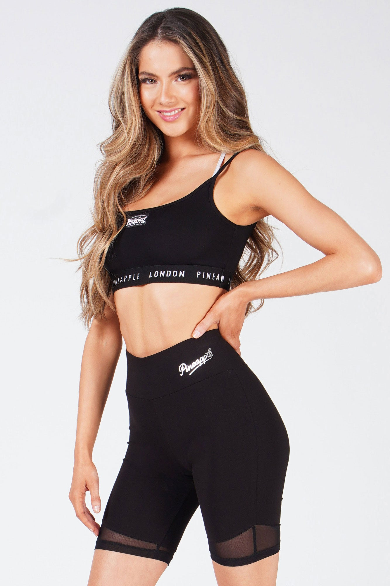 Woman wearing Cross Strap Black Bra Top and black cycling shorts
