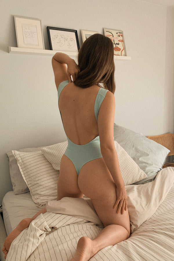 Model posing in mary young mint green backless thong bodysuit