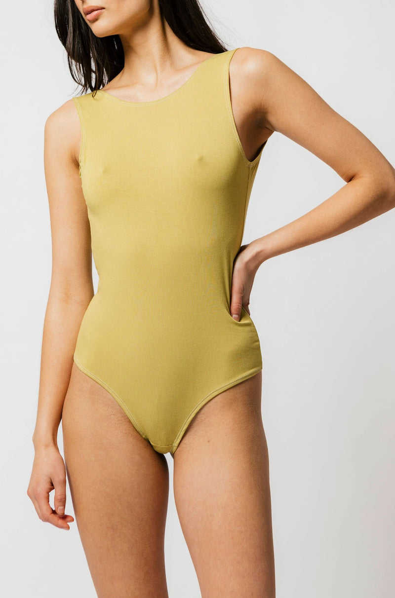 Model posing in mary young matcha green backless thong bodysuit