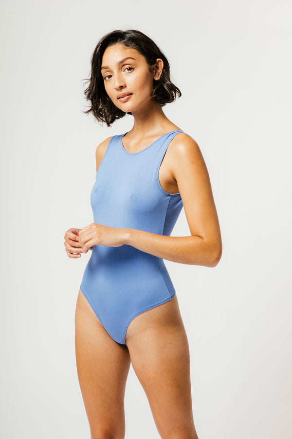 Model with short hair posing in mary young cornflower blue backless thong bodysuit
