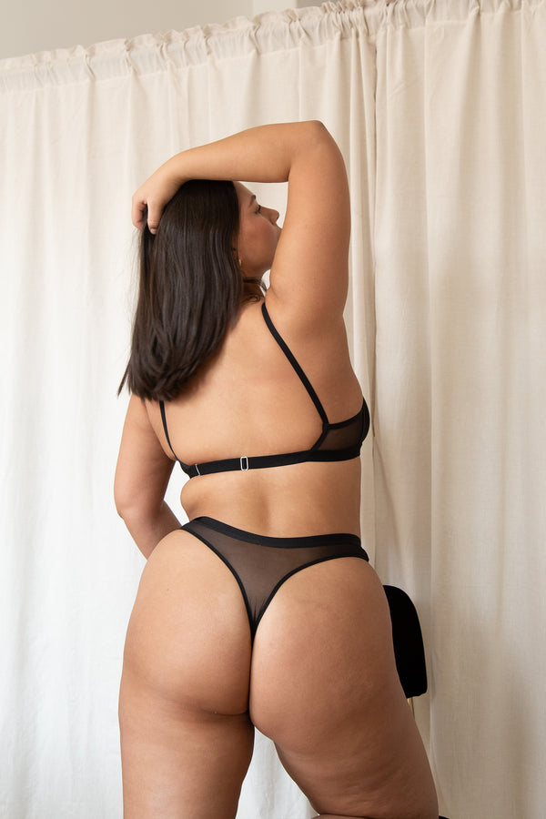 woman stretching in large mesh thong in black