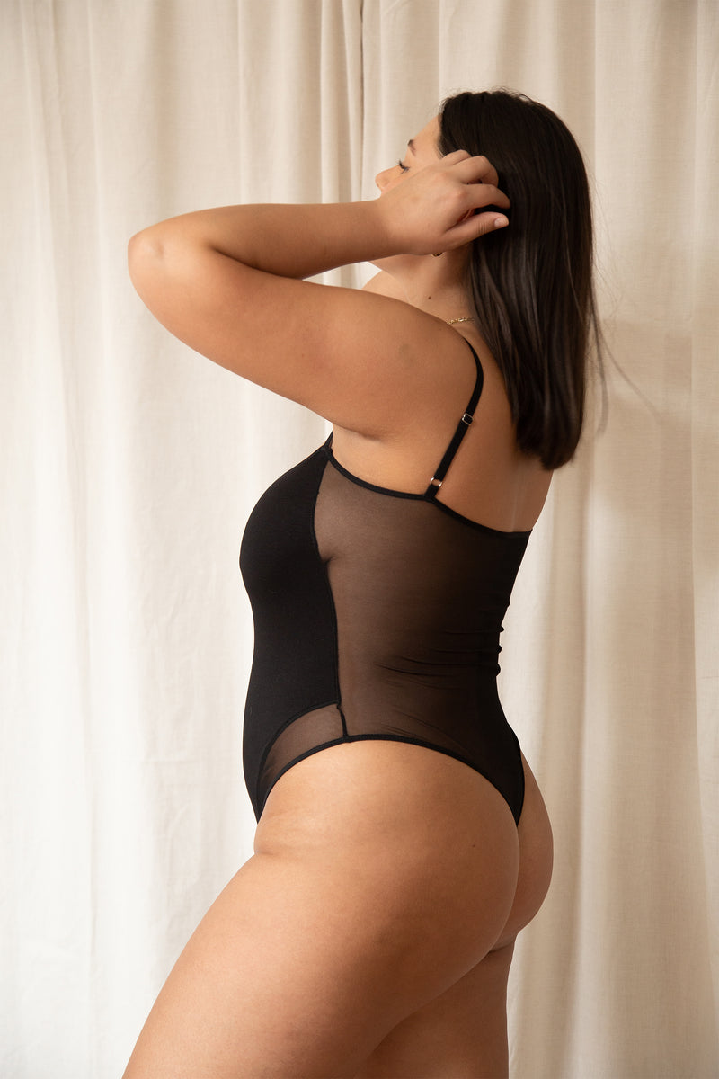 side profile of woman in black bamboo rayon and mesh thong bodysuit