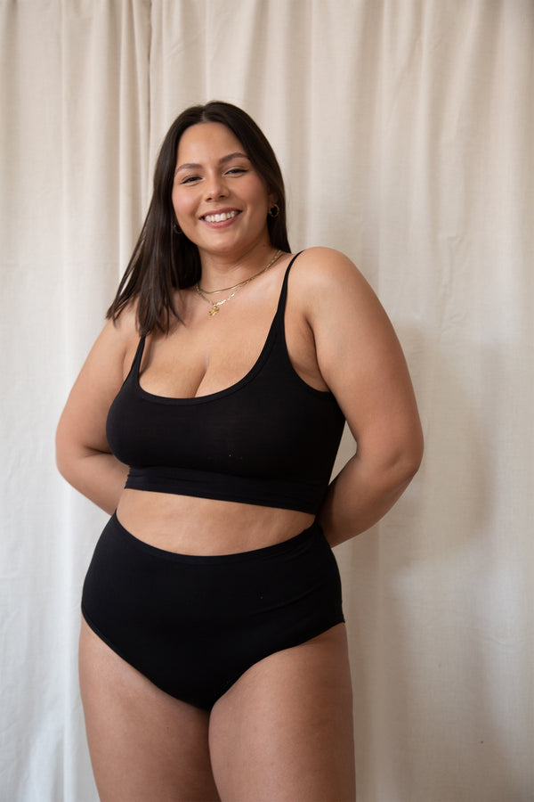 model smiling while wearing black tank top and high waist underwear.