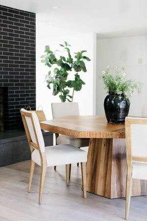 greige design shop + interiors asymetrical dining table and white upholstered dining chairs black tile fireplace