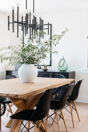 greige design shop + interiors laguna beach cottage dining room black dining chairs natural wood robert abbey chandelier black