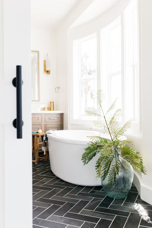 greige design shop + interiors master bathroom herringbone slate floors black with white grout freestanding tub brass fixtures