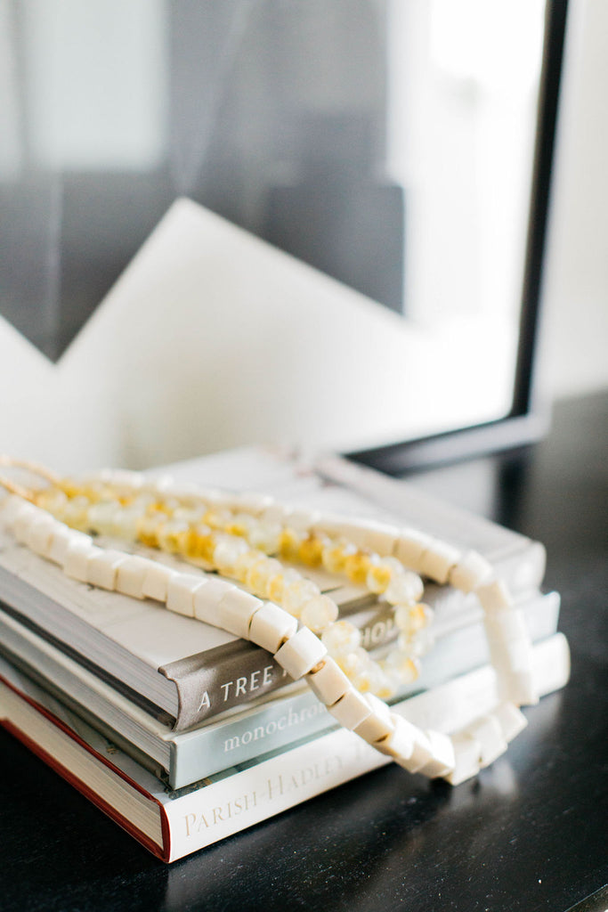 greige design shop + interiors living room yellow glass beads cocktail table books oragami artwork