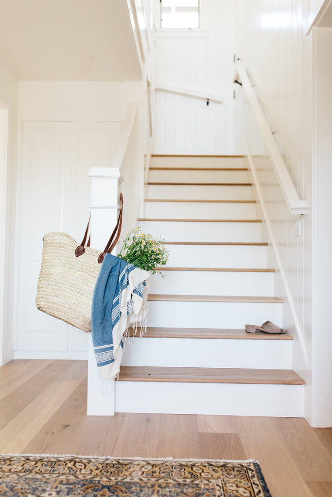 Bright white modern California Coastal retreat entryway stairs with white risers by greige design shop + interiors in Laguna Beach, Ca.