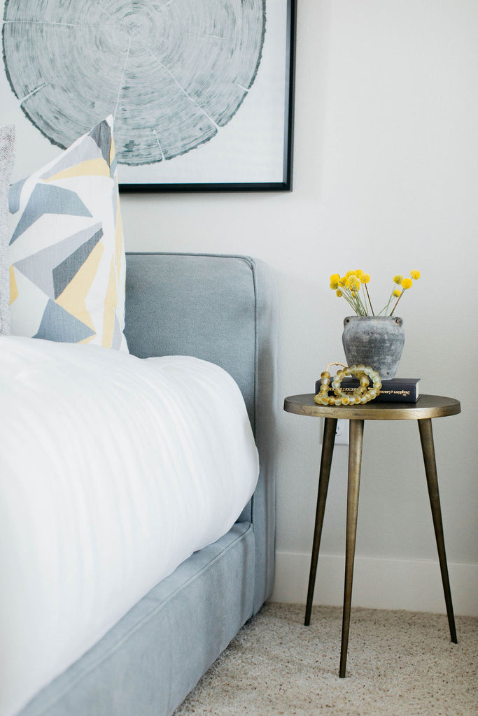 greige design shop + interiors grey and yellow bedroom with brass table grey upholstered bed