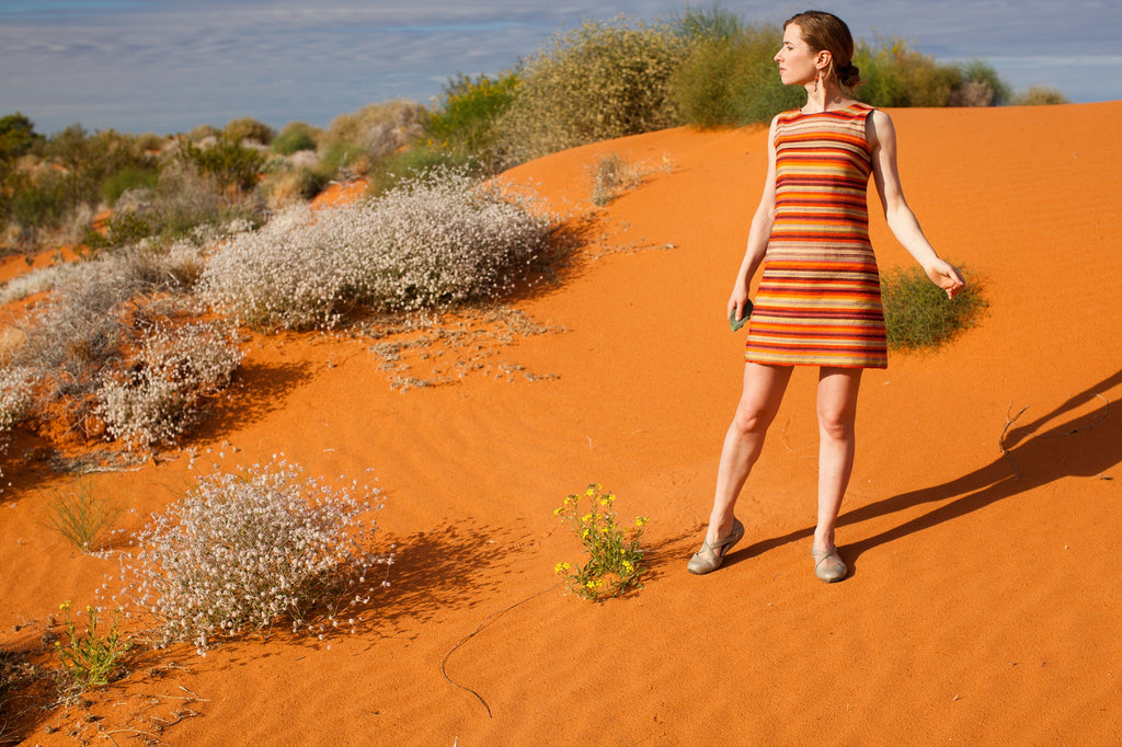 A 1960's style stripy orange dress, orange earrings, photographed in the Simpson Desert