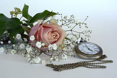 A picture of wedding flowers and a pocket watch