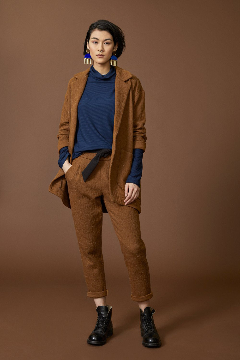 Abell jacket by Cokluch; blazer-like; thick cinnamon crinkle material; large pockets; single button closure; full-length front view; paired with matching pants, a cobalt blue top, and black lace-up boots
