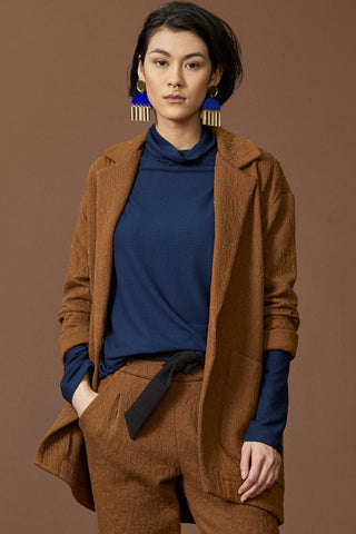 Abell jacket by Cokluch; blazer-like; thick cinnamon crinkle material; large pockets; single button closure; detail front view; paired with matching pants and a cobalt blue top
