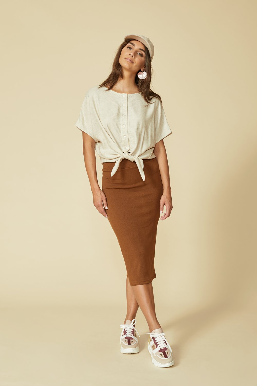 Balance skirt by Cokluch in Tobacco; warm cinnamon shade; slim fitting; high-waisted; hits below the knee; full-length front view; styled with a cream top and neutral sneakers