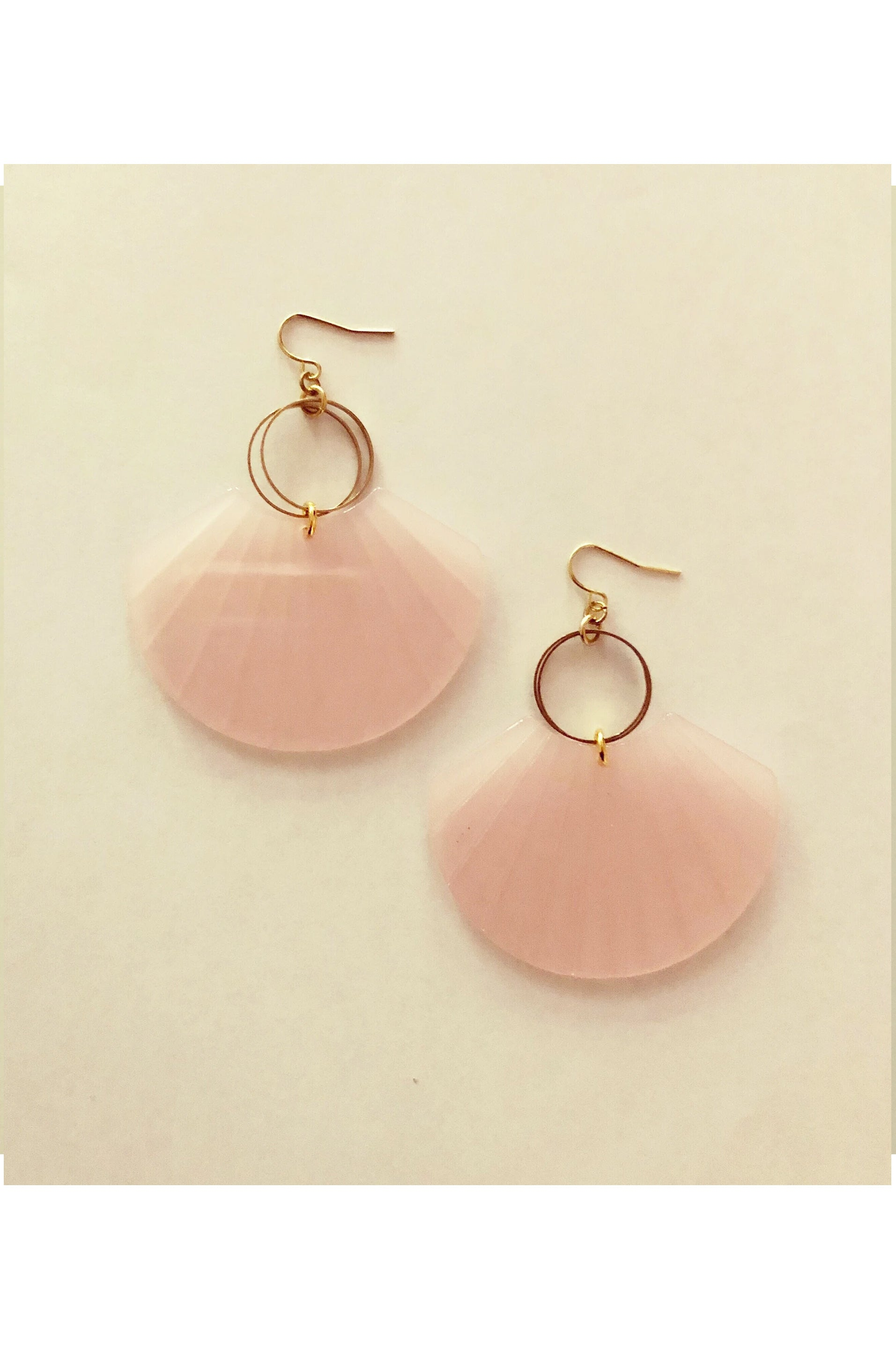 Buelle earrings by Darlings of Denmark; translucent pink; acryclic and raw brass; shell shape hanging off of two slim loops; flat lay