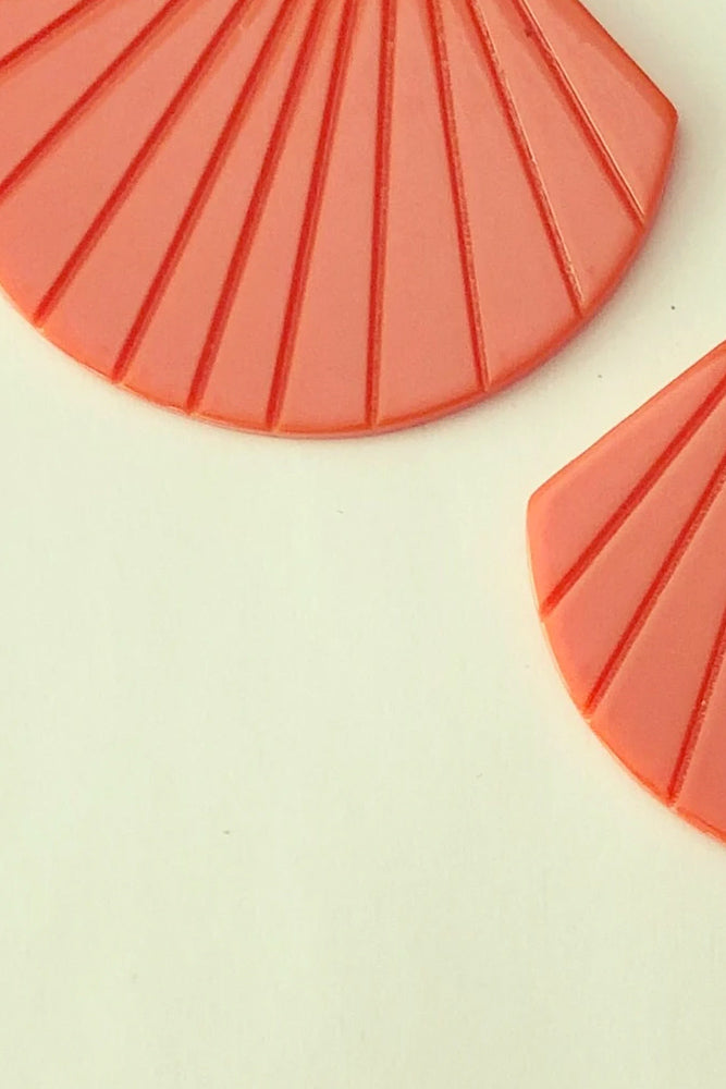 Buelle earrings by Darlings of Denmark; vibrant orange; acryclic and raw brass; shell shape hanging off of two slim loops; flat lay, up close shot