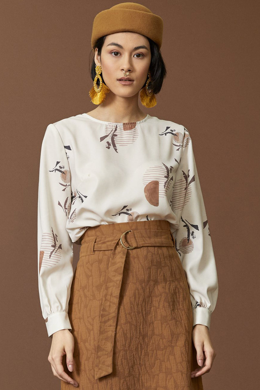 Carene Blouse by Cokluch; cream, warm-tone graphic pattern; rounded neck; long-sleeved, puffy sleeve detail; full-length view; styled with a long, high-waisted, burnt orange skirt and black boots.