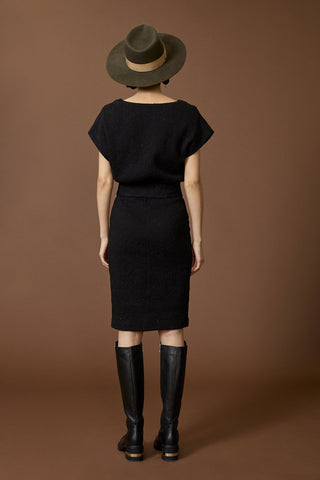 Casiopee dress by Cokluch; straight cut; short-sleeved; black crinkle material; belt at the waist; knee-length; full length rear view, styled with black knee-high boots