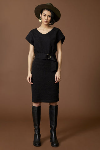 Casiopee dress by Cokluch; straight cut; v-neckline; short-sleeved; black crinkle material; belt at the waist; knee-length; full length front view, styled with black knee-high boots