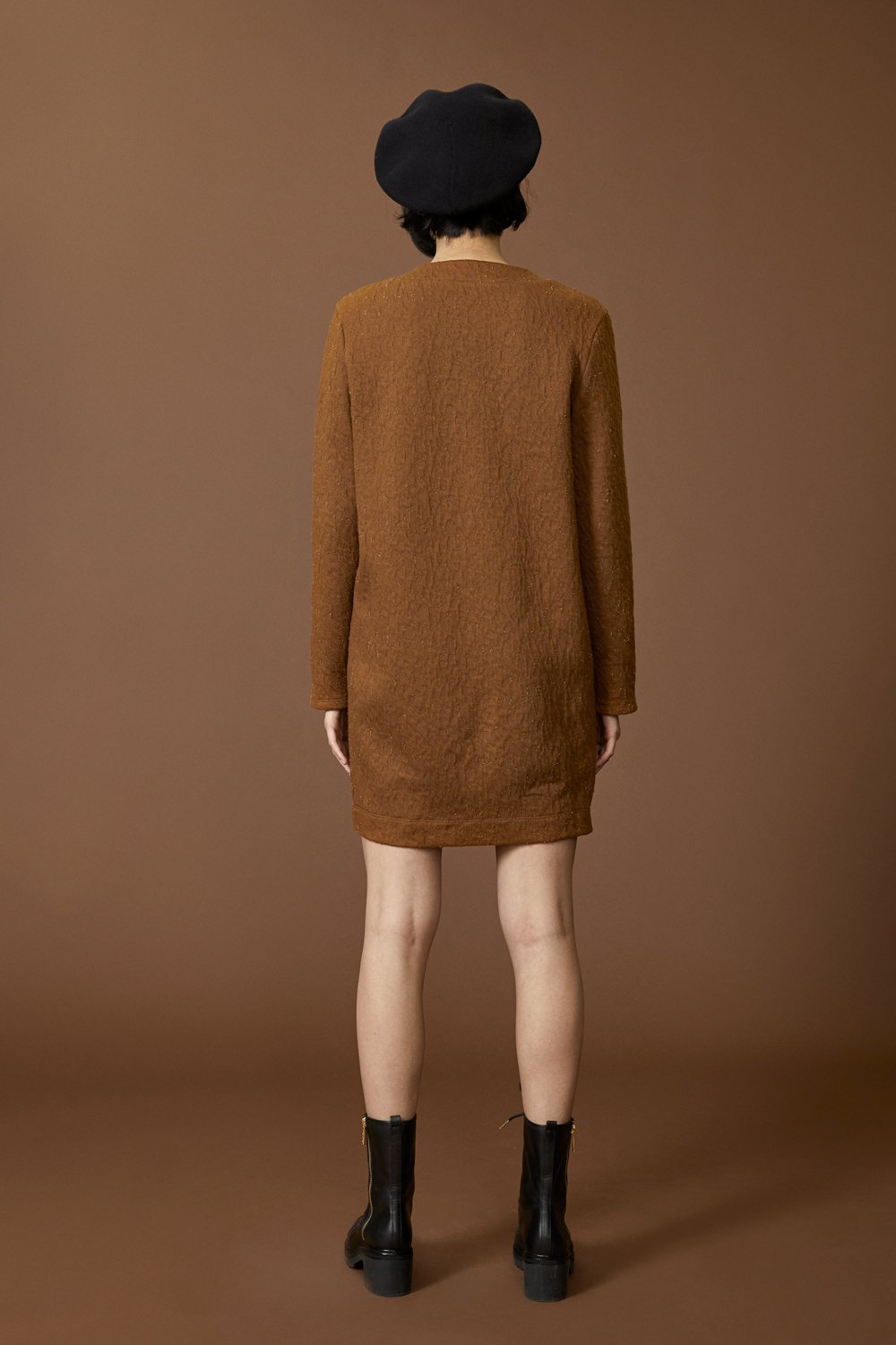 Faye tunic by Cokluch; round neck; long-sleeved; hits above the knee; cinnamon crinkle material; full length rear view, styled with black combat boots