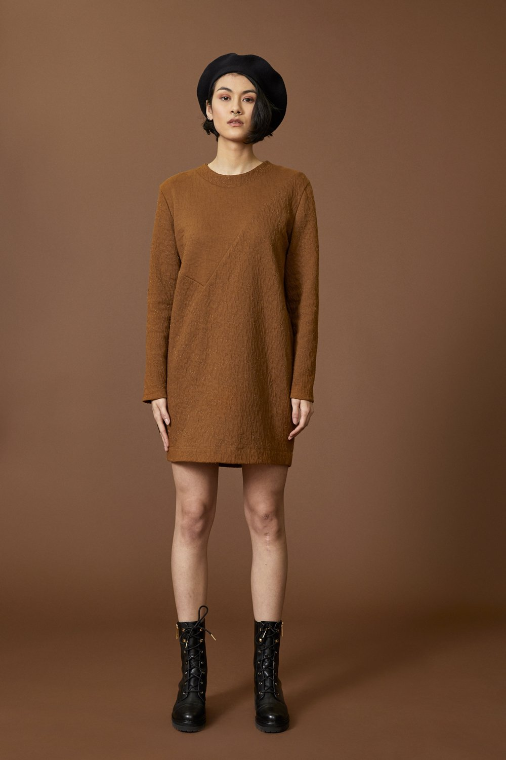 Faye tunic by Cokluch; round neck; long-sleeved; hits above the knee; asymmetrical yoke at the front; cinnamon crinkle material; full length front view, styled with black combat boots