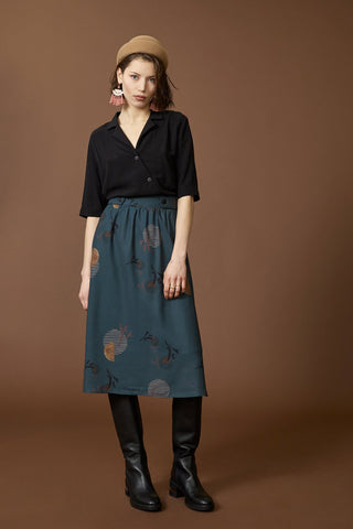 Hill long skirt by Cokluch; teal with a graphic pattern; high-waisted; full-length, front view; styled with a black blouse, black knee-high boots, and a tan tuque