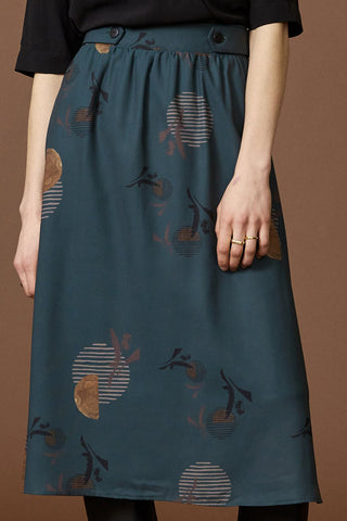 Hill skirt by Cokluch; teal with a graphic pattern; gathers at the waist; hits below the knee; detailed view