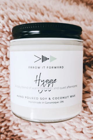 Hygge candle by Arrow It Forward in a reusable glass jar, styled on a cozy, plush blanket
