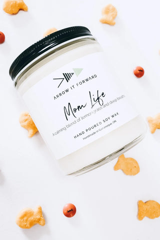 Mom Life candle by Arrow It Forward in a reusable glass jar, styled with Goldfish crackers and Advil