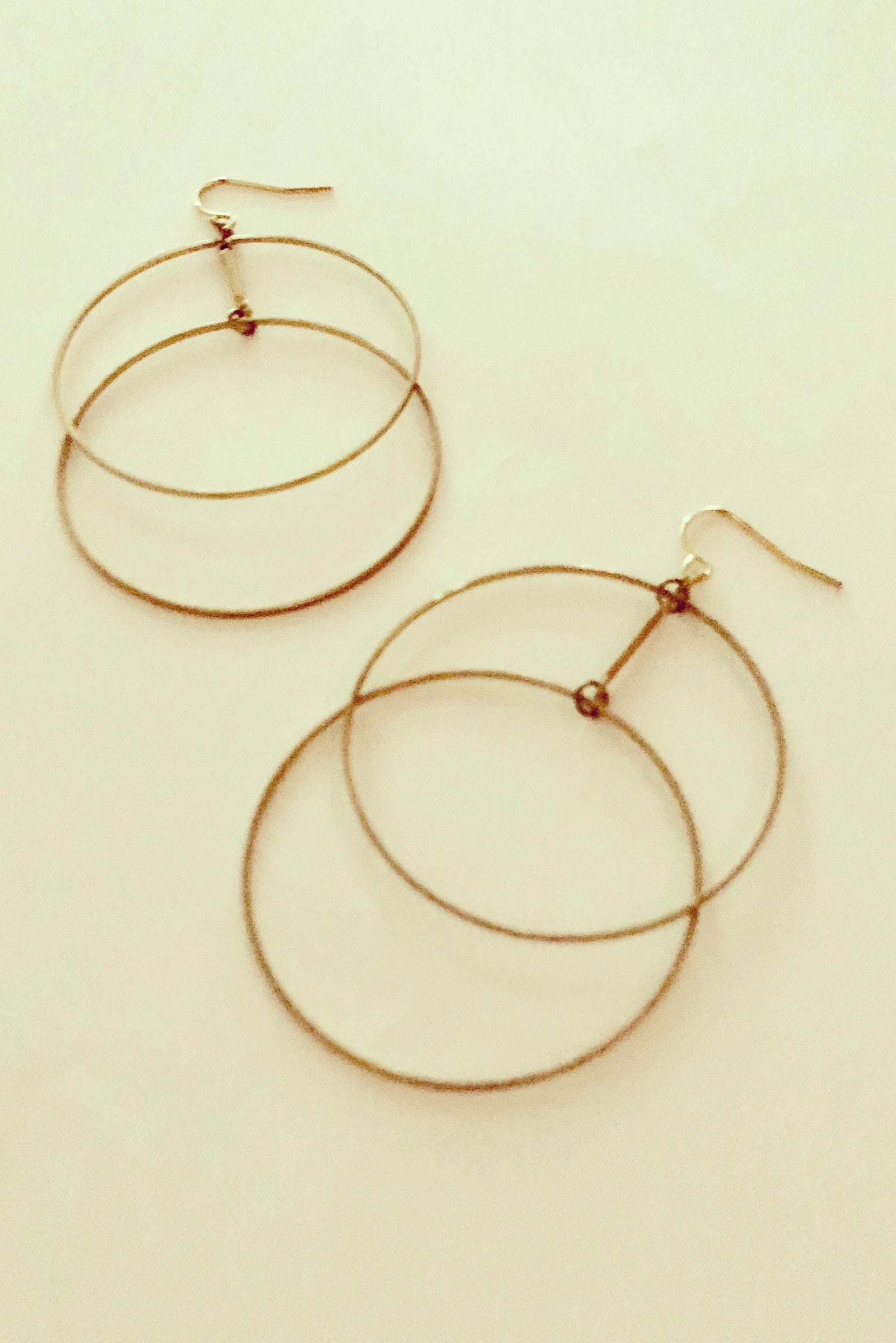 Ruuye earrings by Darlings of Denmark; raw brass; delicate, thin, staggered, double-hoop earrings; flat lay