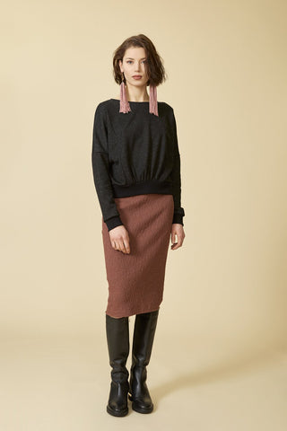 Sagittaire sweatshirt by Cokluch; black speckled material; boat neckline; drop-shoulder; pleat detailing at the waist; full-length front view; styled with a long blush skirt, black knee-high boots; and statement earrings
