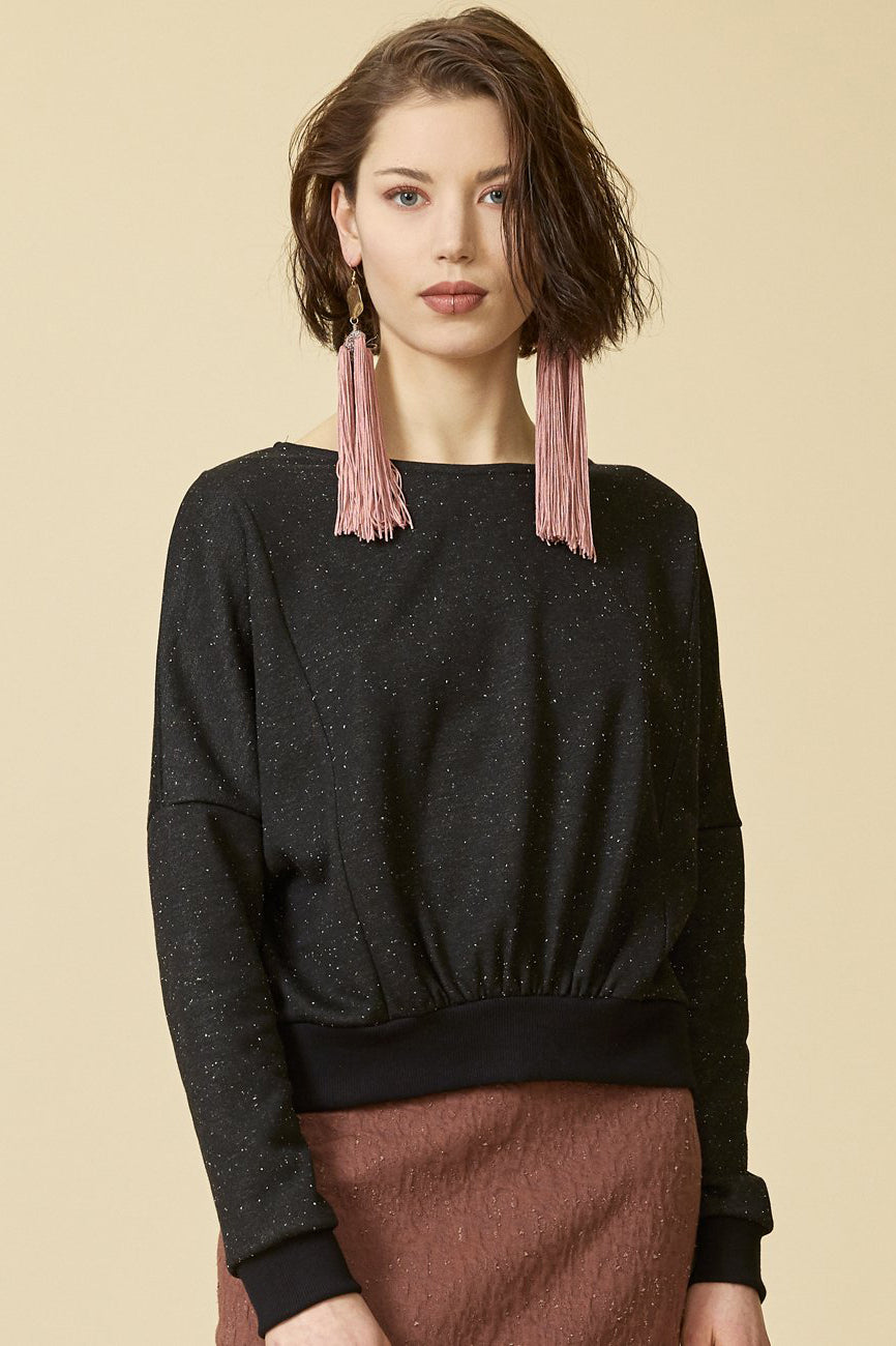 Sagittaire sweatshirt by Cokluch; black speckled material; boat neckline; drop-shoulder; pleat detailing at the waist; detailed front view; styled with a blush skirt and statement earrings.