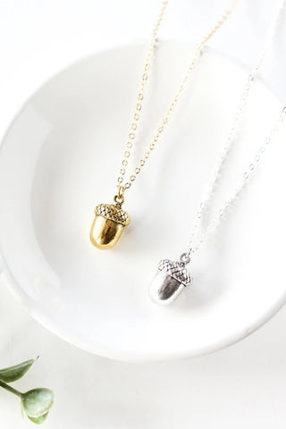 Tiny acorn necklace by Birch Jewellery, in silver and gold, styled on a white ceramic dish