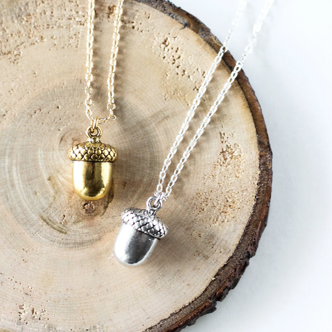 Tiny acorn necklace by Birch Jewellery, in silver and gold, styled on a stump of wood
