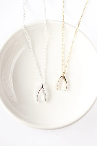 Wishbone necklace by Birch Jewellery; silver and gold plated brass; styled on a white ceramic dish; overhead view