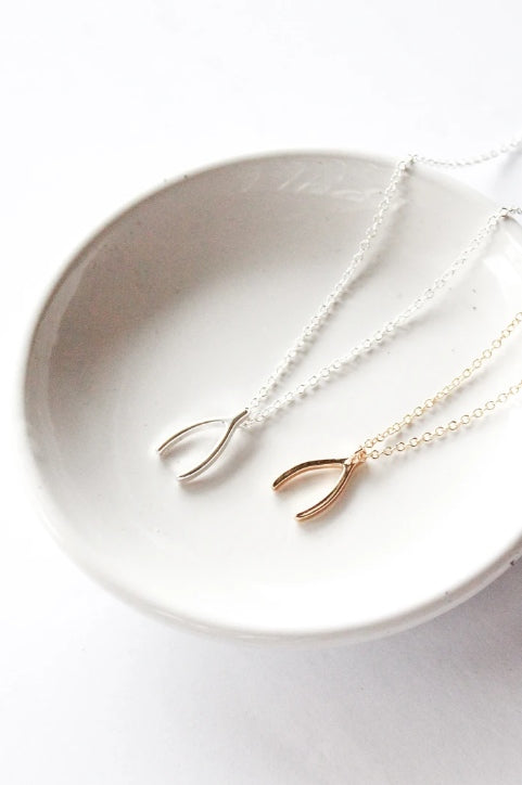 Wishbone necklace by Birch Jewellery; silver and gold plated brass; styled on a white ceramic dish