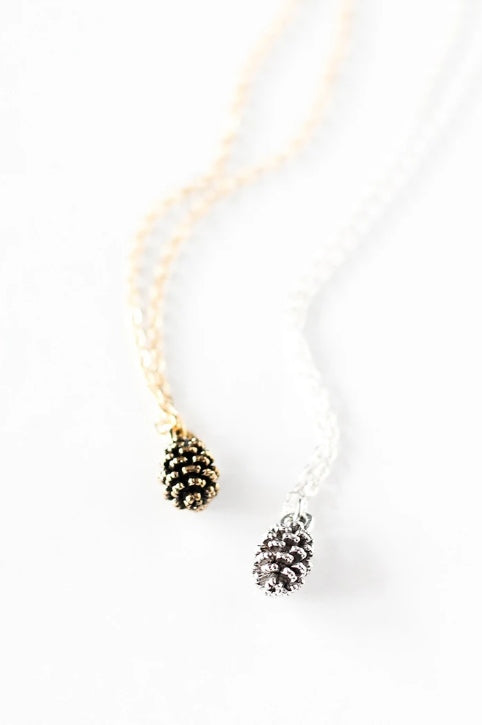 Tiny pine cone necklace by Birch Jewellery in silver and gold, flat lay