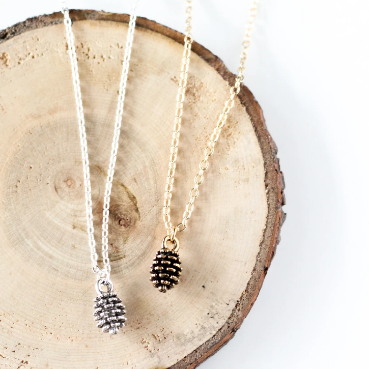 Tiny pine cone necklace by Birch Jewellery in silver and gold, styled on a stump of wood
